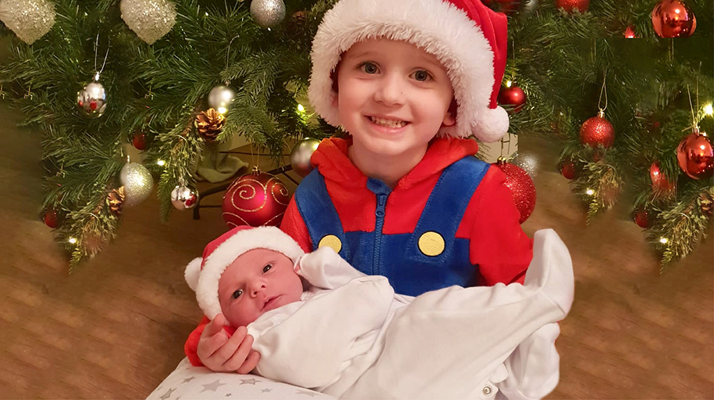 My two boys sitting under the christmas tree wearing hearing aids and cochlear implants